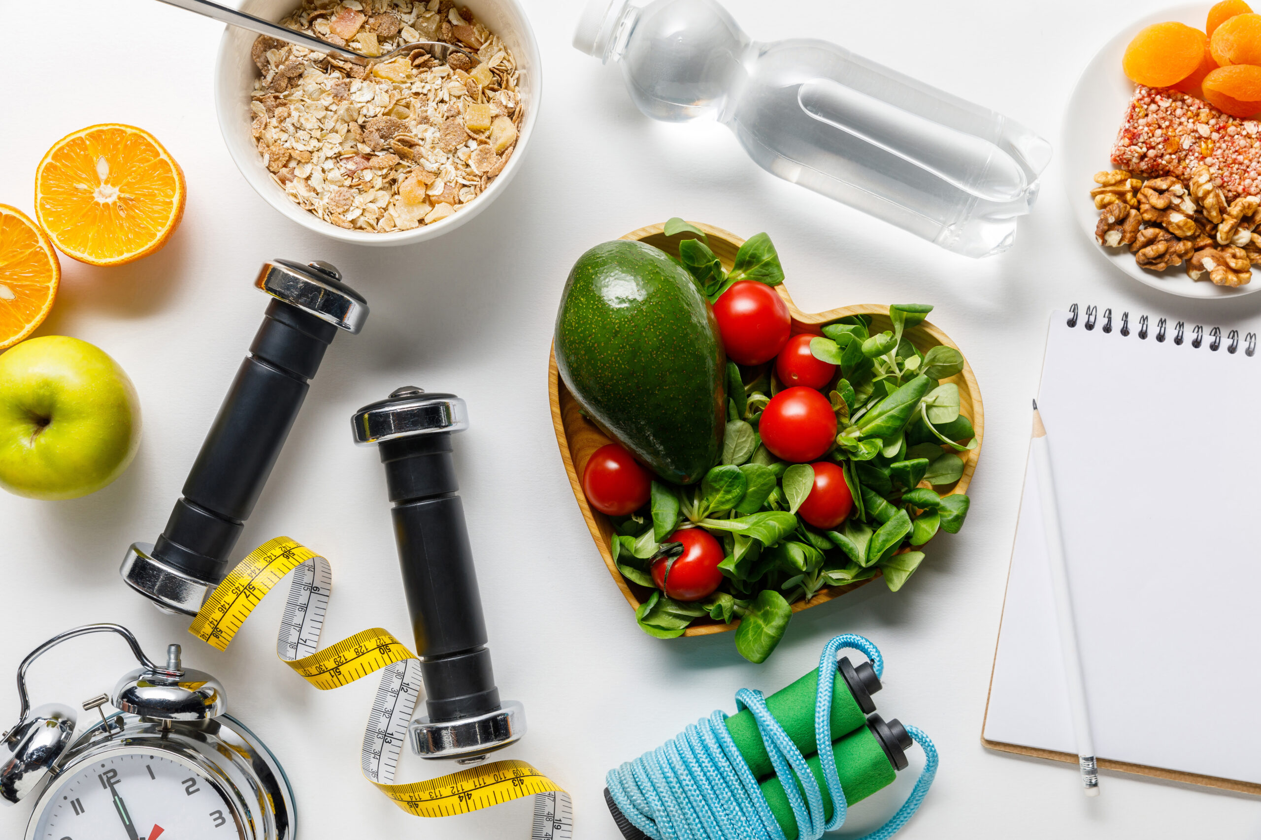 top view of sport equipment, measuring tape, alarm clock and notebook near diet food and water on white background